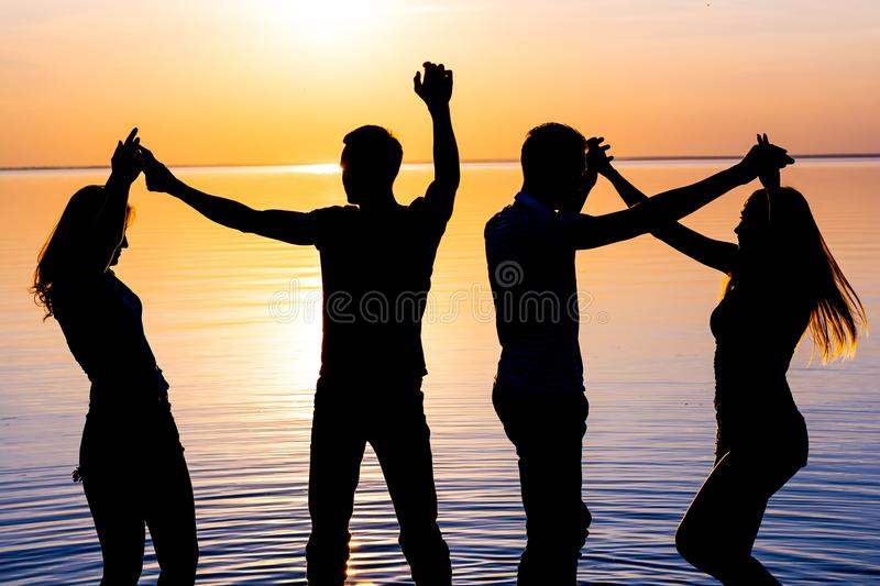 Young people, guys and girls are dancing couples at sunset background, silhouettes stock images