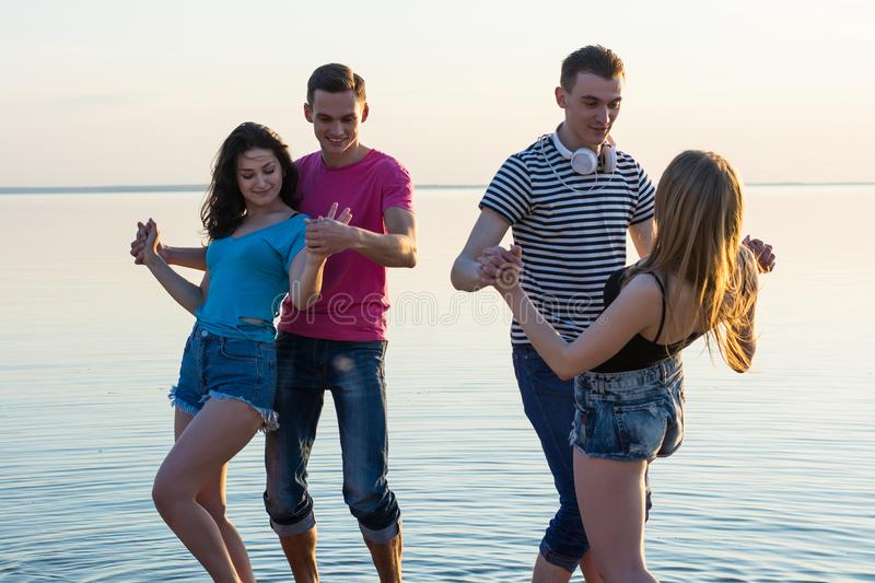 Young people, guys and girls, students are dancing couples in fr. Ont of a sea royalty free stock image