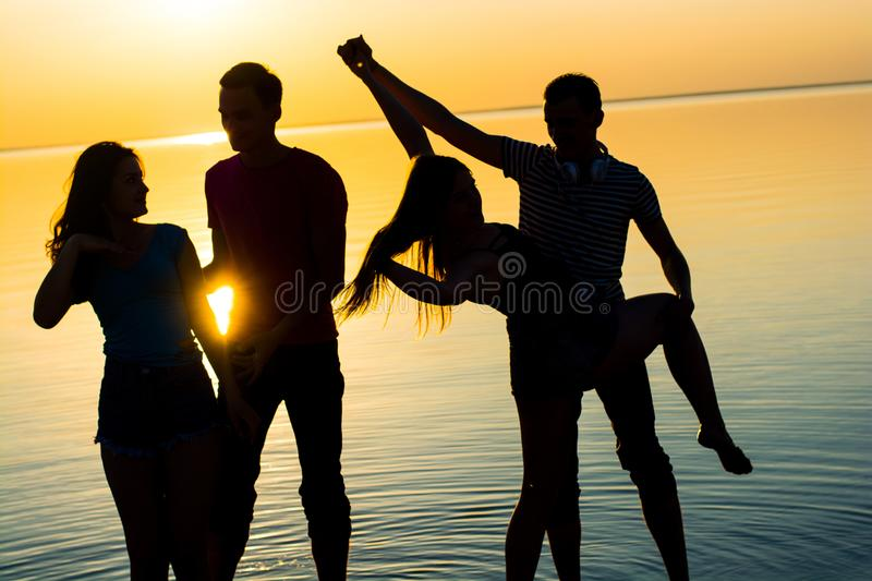 Young people, guys and girls, students are dancing couples at sunset background. Silhouettes royalty free stock photos