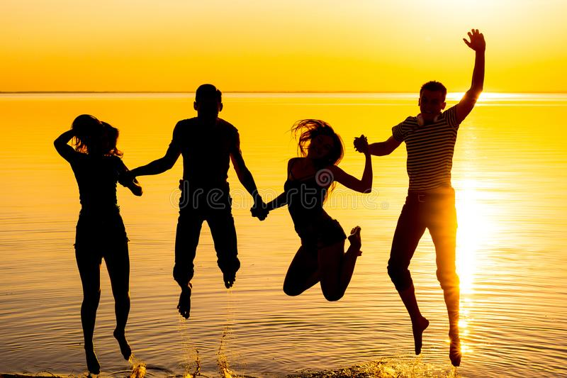 Young people, guys and girls, students are jumping against the sunset background stock photography