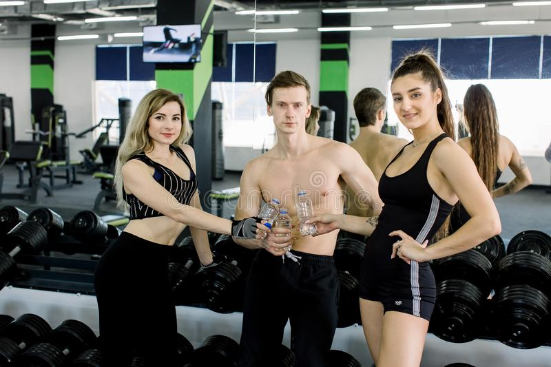 Young people in the gym, Beautiful young friends in sports clothes, holding water bottles, looking at camera and smiling royalty free stock image