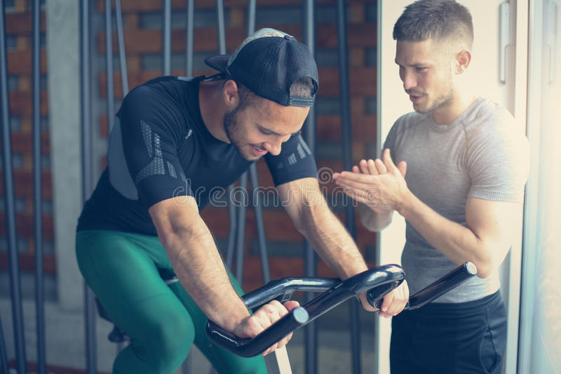 Young people in gym. Friends workout in gym and using smart phone. stock photography