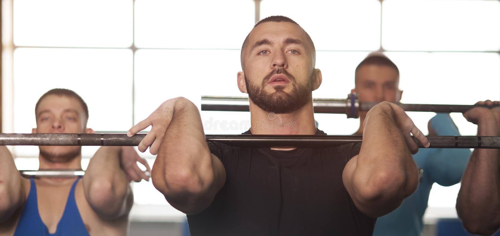 Young People in Gym Training With Barbells royalty free stock images