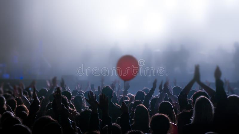 Young people with hands in the air during rock concert silhouetted against bright lights royalty free stock photo