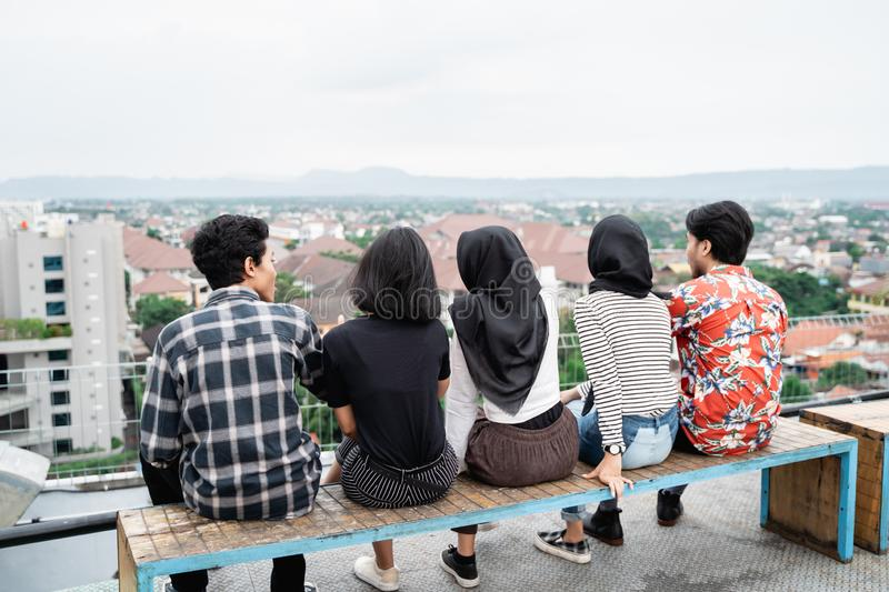 Young people hanging out on the building rooftop stock image