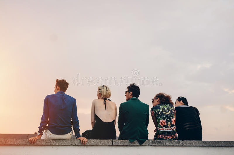 Young people hanging out on rooftop at sunset. Rear view shot of young people hanging out on rooftop at sunset. Young men and women sitting on terrace in evening stock image