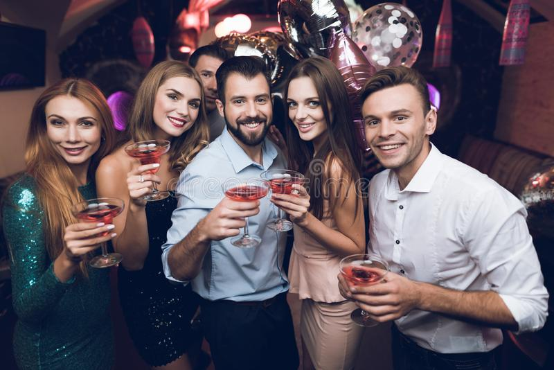 Young people have fun in a nightclub. They drink cocktails and have fun. They are having fun. royalty free stock photo