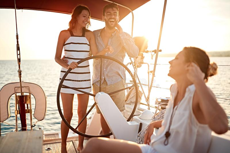 Young people have fun on the yacht at sunset stock photos
