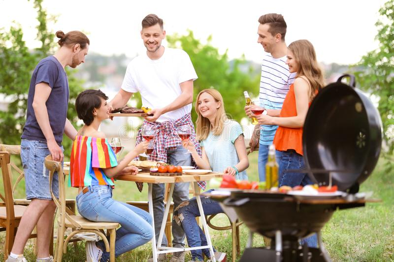 Young people having barbecue with modern grill. Outdoors stock image