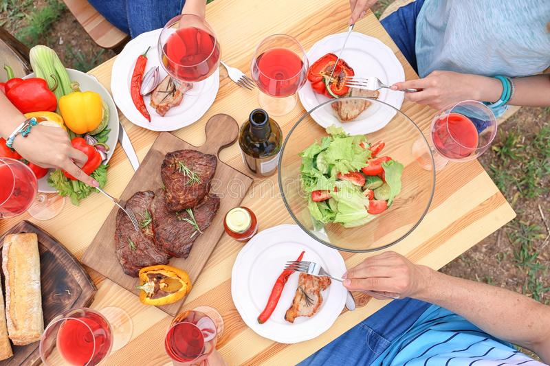Young people having barbecue at table outdoors stock images