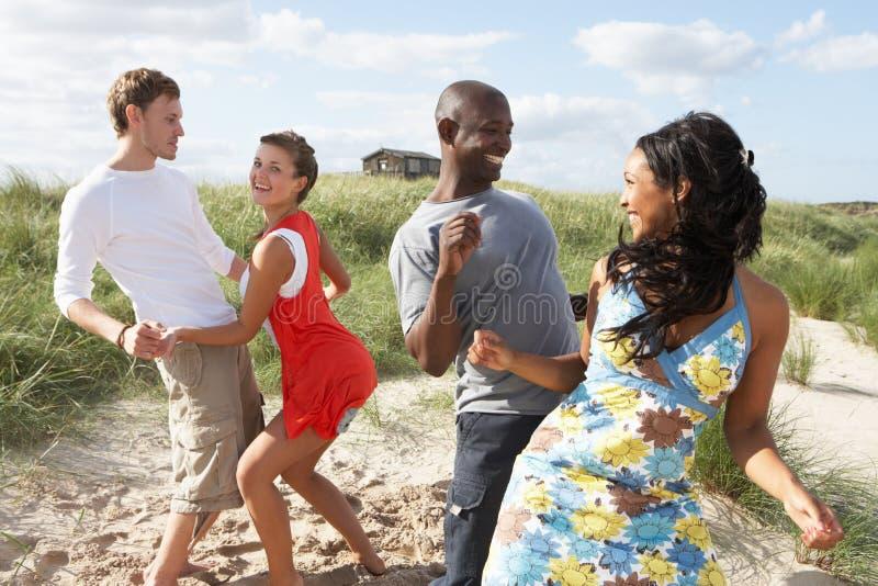 Young People Having Fun Dancing On Beach. Group Of Young People Having Fun Dancing On Beach Together stock photo
