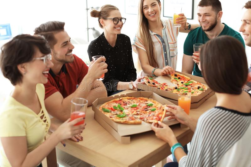 Young people having fun party with delicious pizza royalty free stock photography