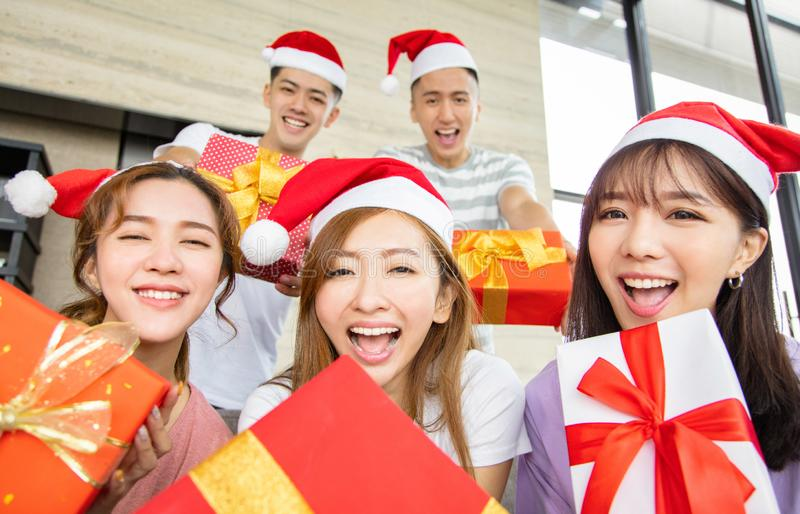 Young people having fun and showing christmas gift stock photos