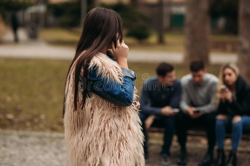 Young people having a good time in park. Male and female sitting on the bench and using phones stock images