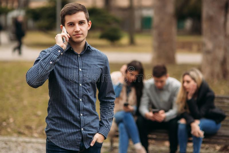 Young people having a good time in park. Male and female sitting on the bench and using phones stock image