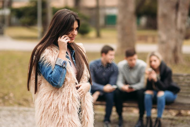 Young people having a good time in park. Male and female sitting on the bench and using phones stock photography