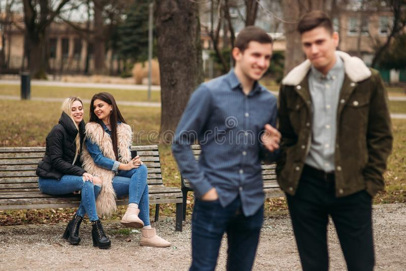 Young people having a good time in park. Male and female sitting on the bench and using phones royalty free stock image