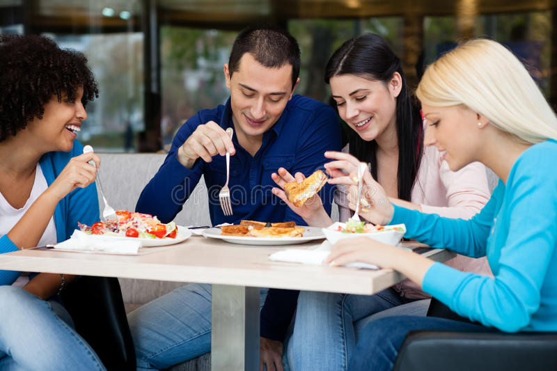 Young people having lunch in restaurant royalty free stock photography