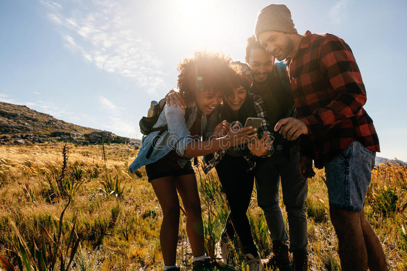 Young people hiking in countryside using mobile phone stock photo