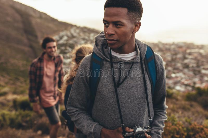 Young people on hiking trip. African men with camera hiking on mountain trail with his friends in background. Young people on hiking trip stock images