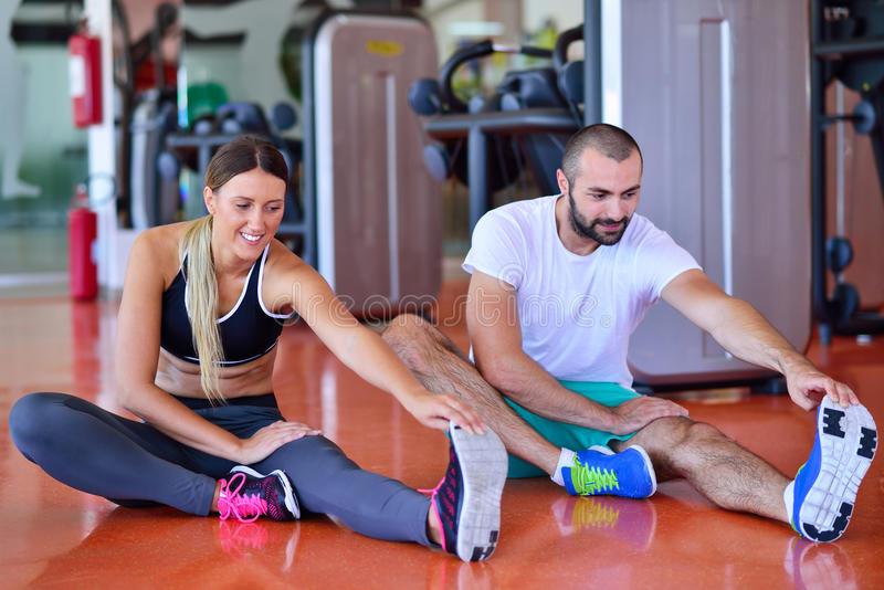 Young people involved in sports. Woman stretching with personal trainer stock photography