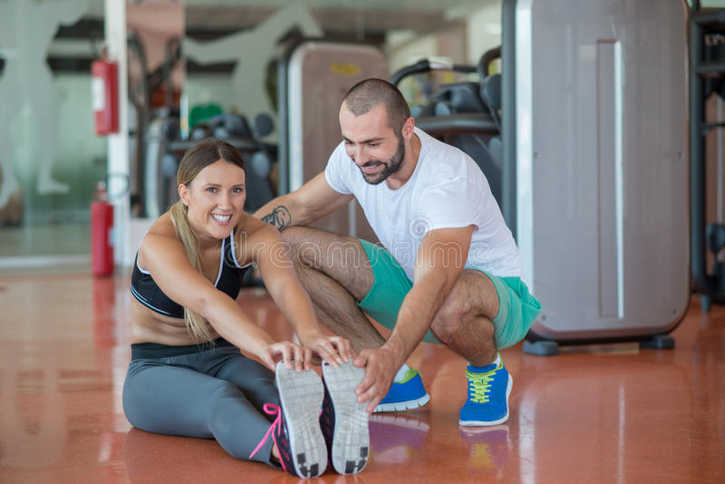 Young people involved in sports. Woman stretching with personal trainer royalty free stock photography