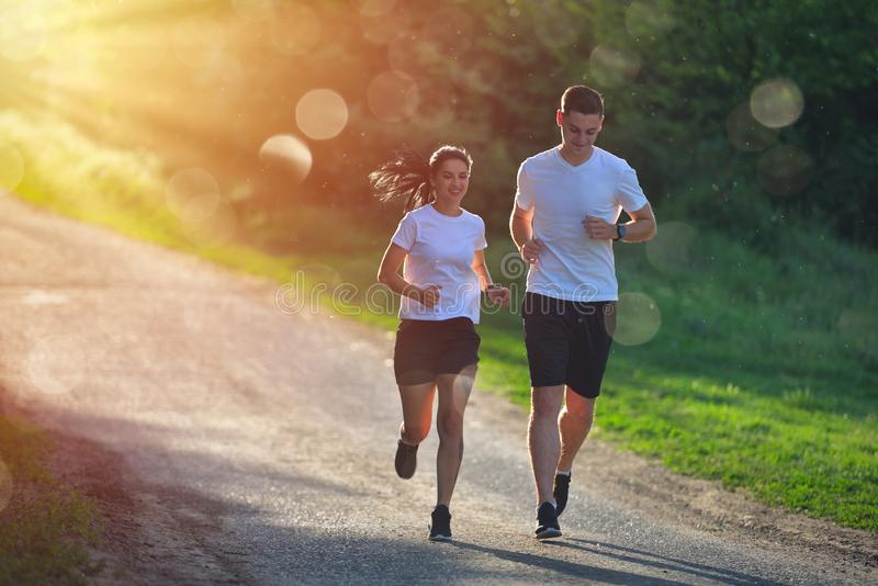 Young people jogging and exercising in nature, in morning sunrise warm light stock images