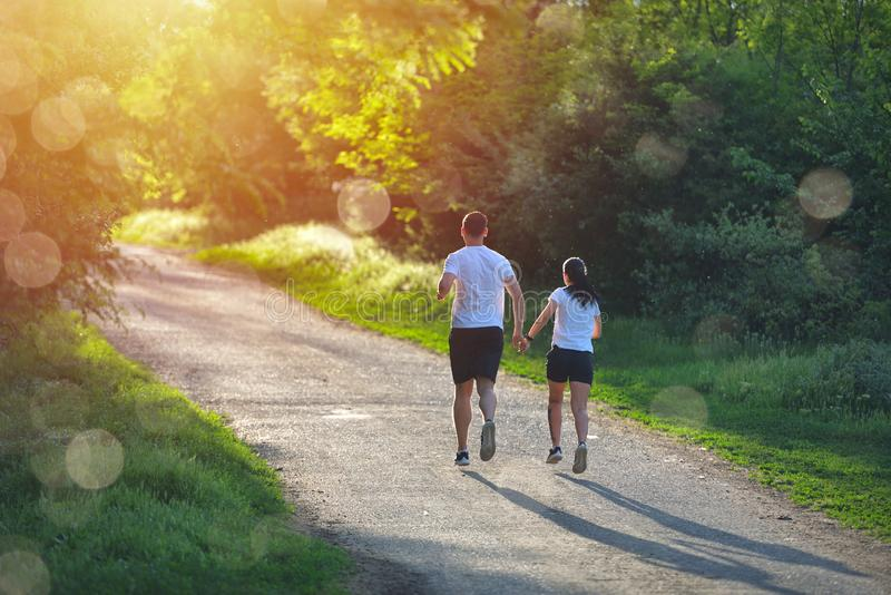 Young people jogging and exercising in nature, in morning sunrise warm light stock image