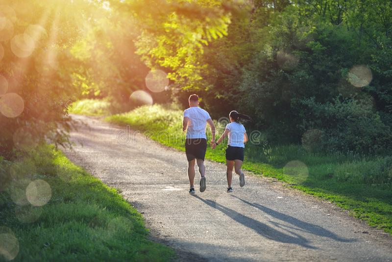 Young people jogging and exercising in nature, in morning sunrise warm light stock photography