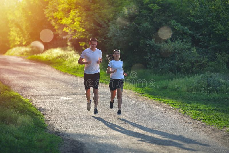Young people jogging and exercising in nature, in morning sunrise warm light royalty free stock photography