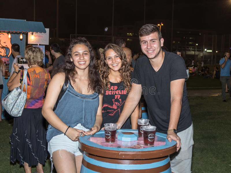 Young people joyfully posing near a decorative beer cask at the traditional annual beer festival in Haifa, Israel. Haifa, Israel, August 16, 2017 : Young people royalty free stock images