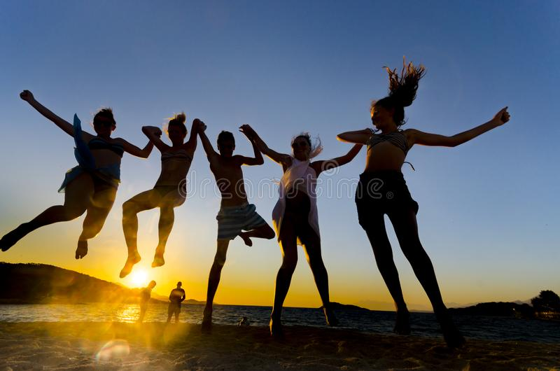 Young people jumping on the beach stock photo