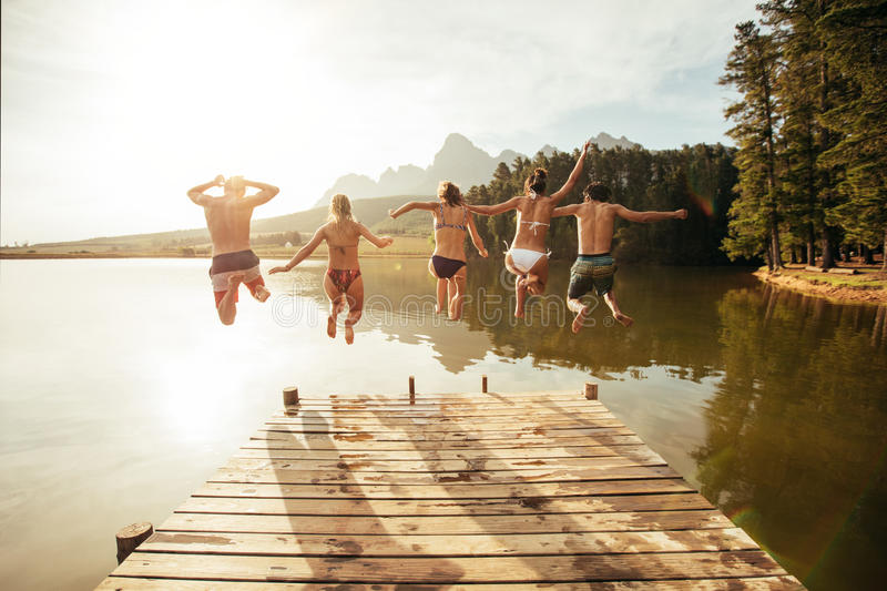 Young people jumping from pier into lake together stock photography
