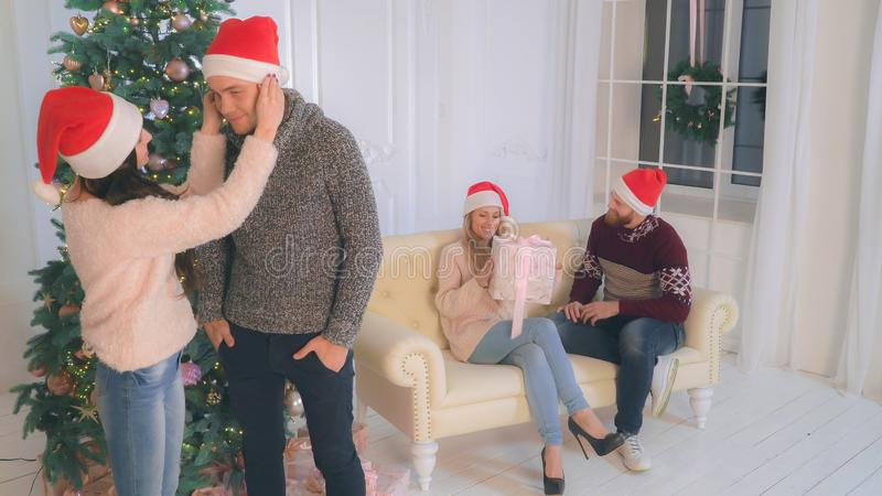 Two couple in love at home wearing in santa hat. stock photography