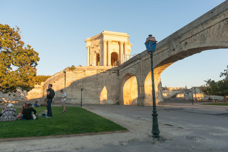 Young people on lawn by aquaduct below Chateau D`Eau or water to. Wer caught in late sun on Promenade du Peyrou Montpellier France Roman urban architecture royalty free stock photo