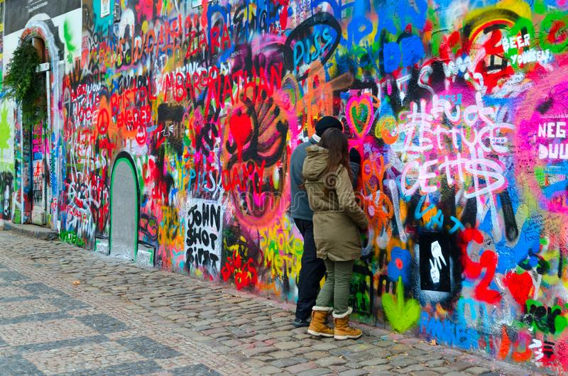 Young people leave inscription on famous John Lennon Wall near Kampa Island in Prague, Czech Republic stock images