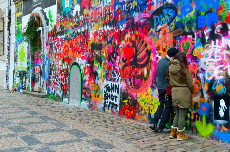 Young people leave inscription on famous John Lennon Wall near Kampa Island in Prague, Czech Republic royalty free stock photos