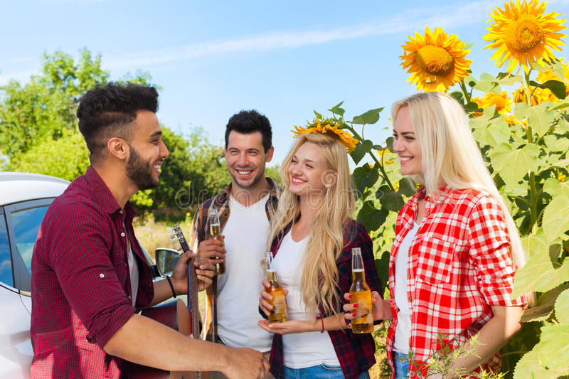 Young people listening guy playing guitar friends drinking beer bottles outdoor countryside. Two couple standing near car happy smile summer sunflower royalty free stock photos