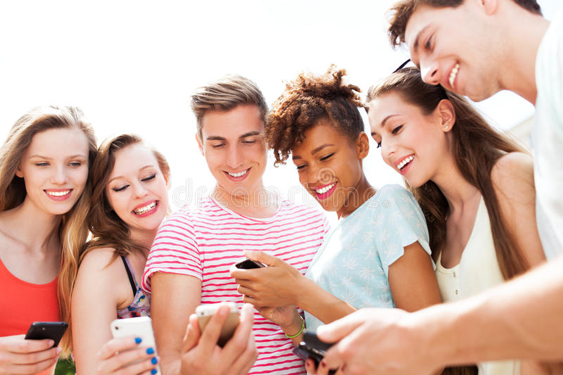 Young people looking at smartphones stock photo
