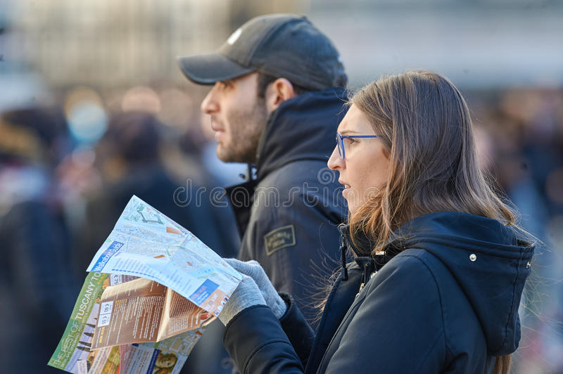 Young people looking for a touristic objectives on map. ITALY- FLORENCE, DECEMBER 24 2016: Young people looking for a touristic objectives on map in Florence stock photography