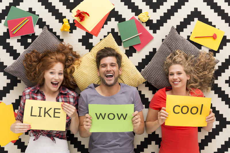 Young people lying on carpet and laughing royalty free stock images
