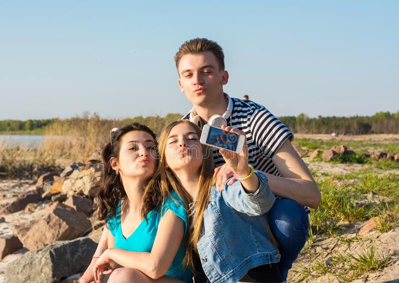 Young people, man and two women, brunette and blonde taking duck royalty free stock images