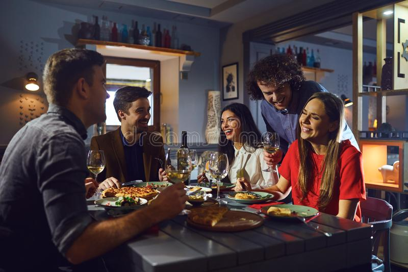 Young people meeting friends for dinner in a restaurant stock photos