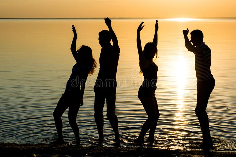 Young people, men and women, students are dancing at sunset back. Young people, guys and girls, students are dancing couples at sunset background, silhouettes royalty free stock image