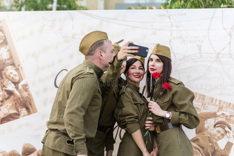 Young people in military uniform of the Great Patriotic War, make selfie on your smartphone stock images