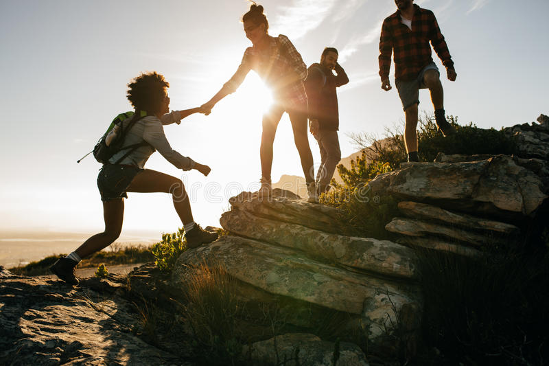 Young people on mountain hike at sunset stock images