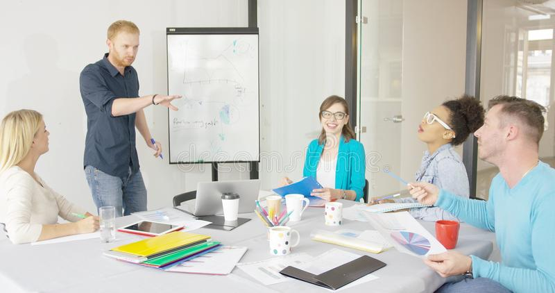 Young people in office sharing ideas stock photo