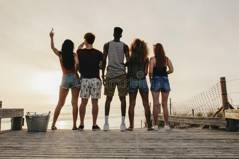 Young people partying at beach. Rear view of friends standing at the beach beer bottle at the sunset. Friends having party at the beach in twilight sunset royalty free stock photography