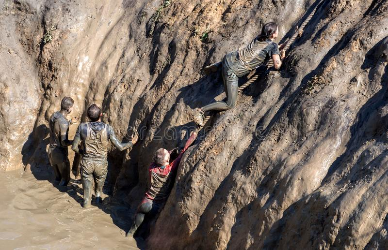 Young people pass the obstacle course. Mud race runners. All in the mud. Deep dirty pit, climb the rope stock photography