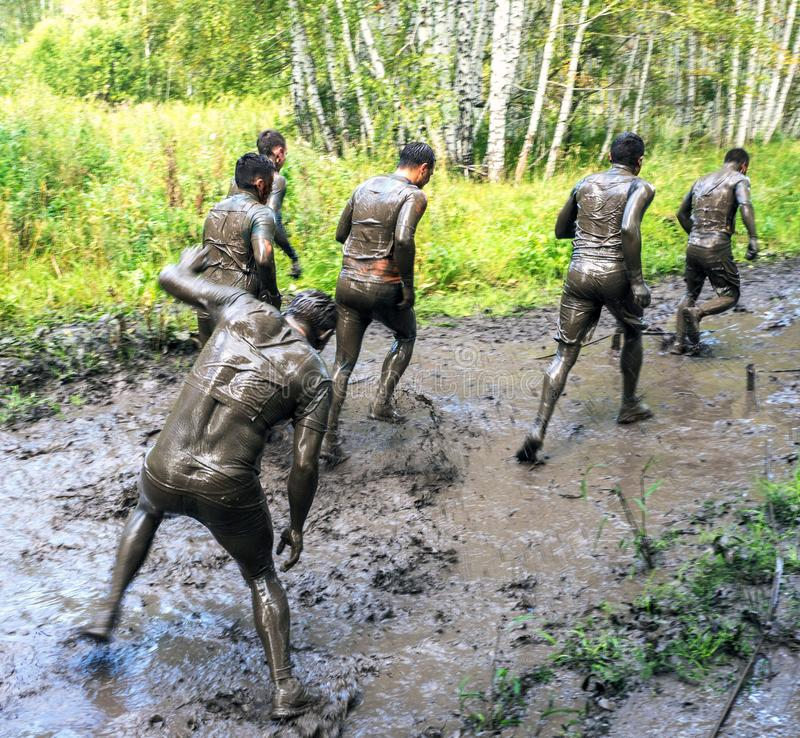 Young people pass the obstacle course. Mud race runners. Teamwork royalty free stock photos